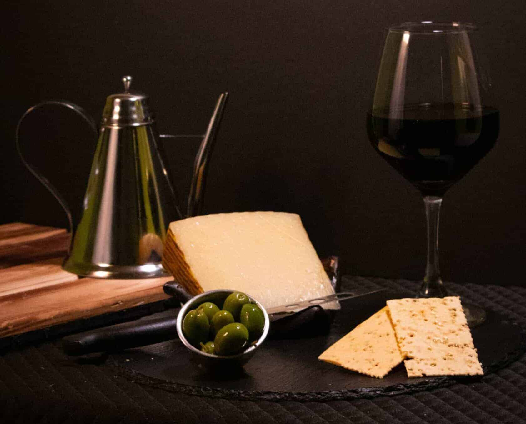 Manchego Cheese served with wine & olives